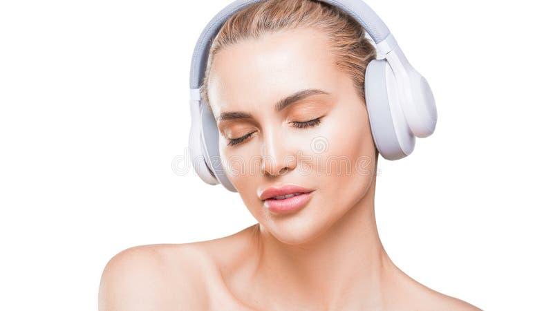 La mujer hermosa en los auriculares blancos escucha la música con los ojos cerrados en el fondo blanco imagenes de archivo