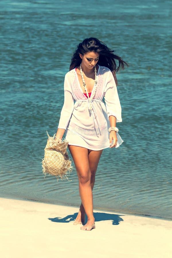 La mujer hermosa en la playa tropical, morenita bronceó a la muchacha que gozaba y que caminaba en la playa fotos de archivo