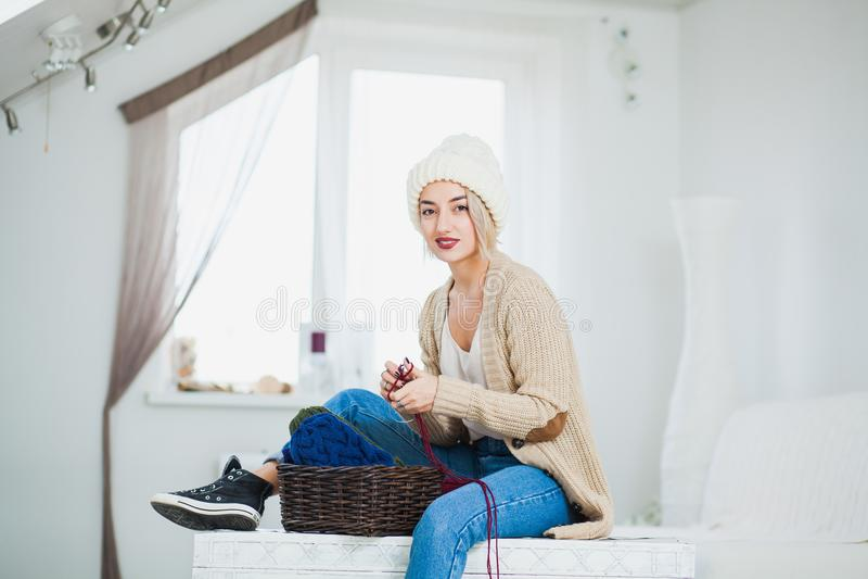 La mujer hermosa en sombrero hecho punto blanco grande dentro se sienta en pecho con hilado de la cesta fotos de archivo