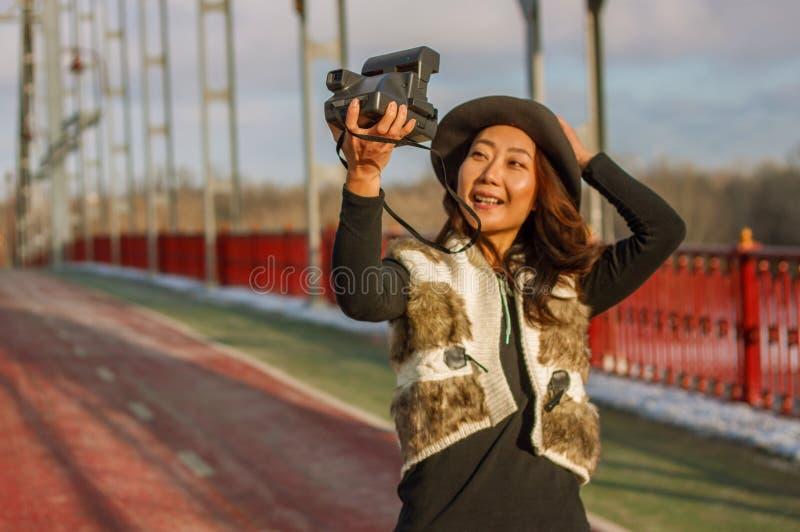La mujer hermosa en sombrero negro hace un selfie polaroid en un puente en el invierno en Europa fotos de archivo
