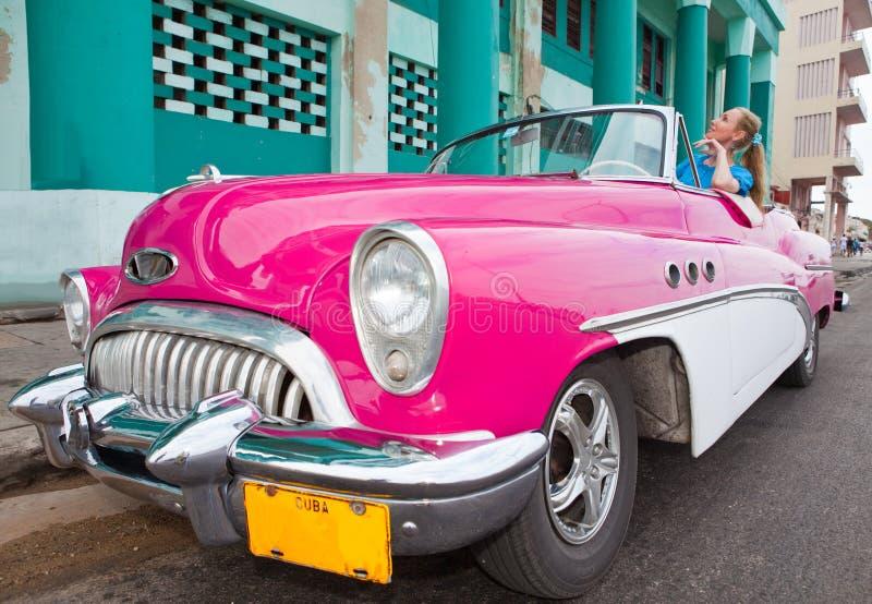 La mujer hermosa en un coche retro americano viejo de la rueda (50.os años del siglo pasado), una vista icónica en la ciudad, en  fotografía de archivo