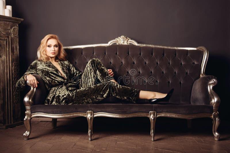 La mujer hermosa en un traje del velor se sienta en un sofá del vintage cerca de una chimenea foto de archivo