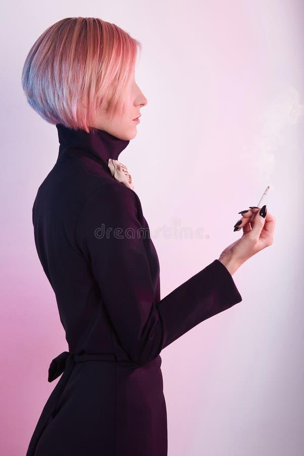 La mujer hermosa en vestido, fuma un cigarrillo fotos de archivo