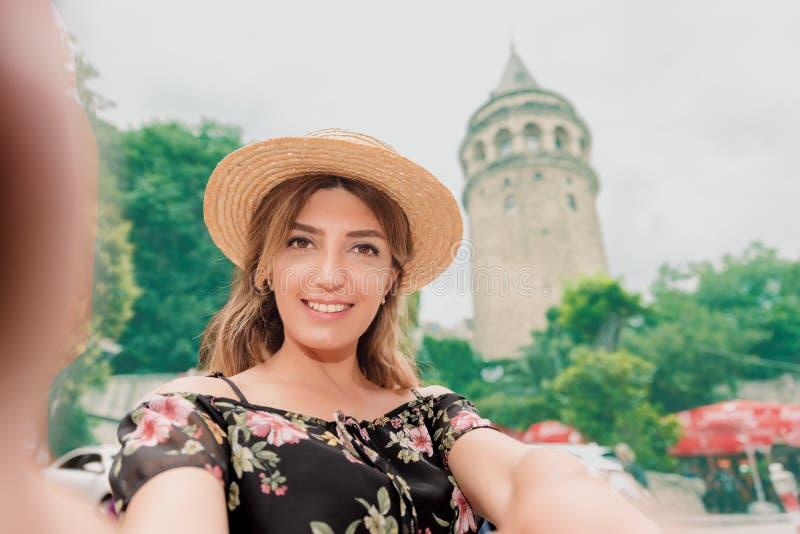 La mujer hermosa en vestido negro toma el selfie delante de la torre de Galata de la señal imágenes de archivo libres de regalías