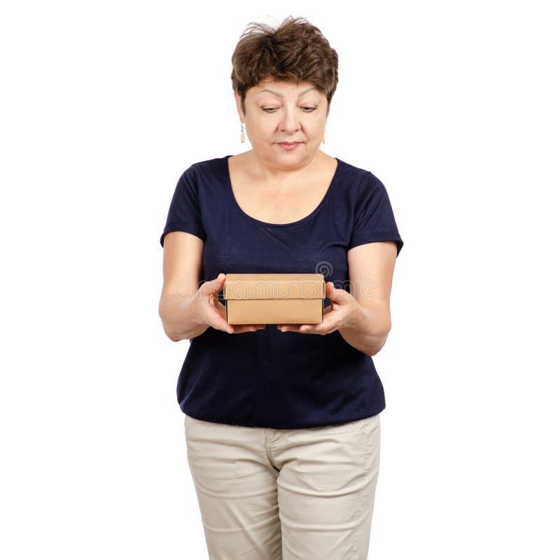 La mujer hermosa envejecida está sosteniendo una caja imagen de archivo