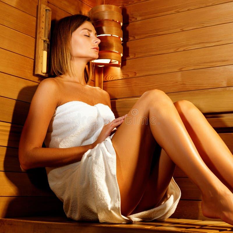La mujer hermosa envuelta en la toalla blanca toma una sauna de madera fotos de archivo