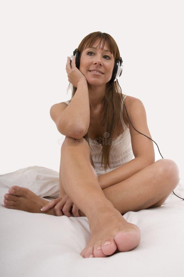 La mujer hermosa escucha música en cama imagen de archivo libre de regalías