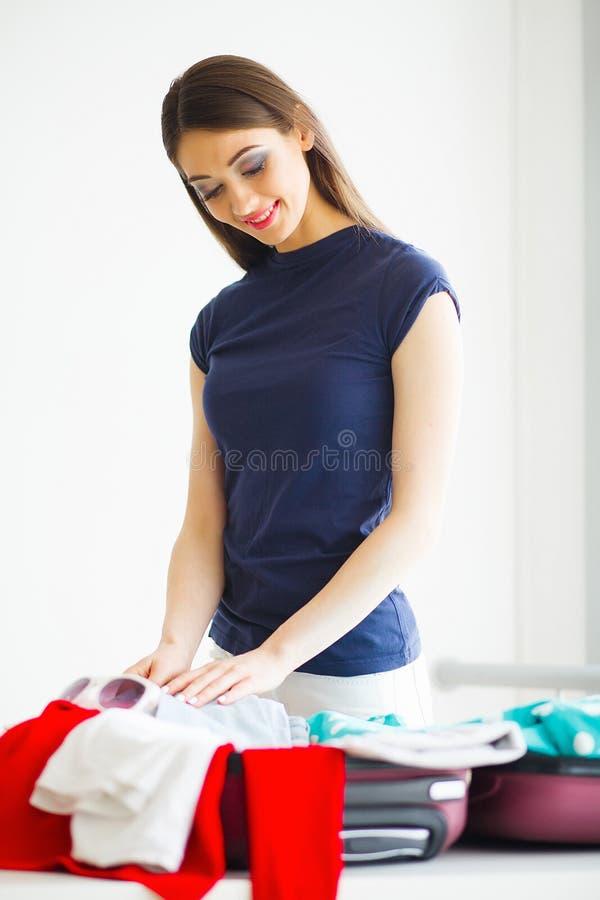 La mujer hermosa está embalando la ropa en maleta en casa foto de archivo libre de regalías