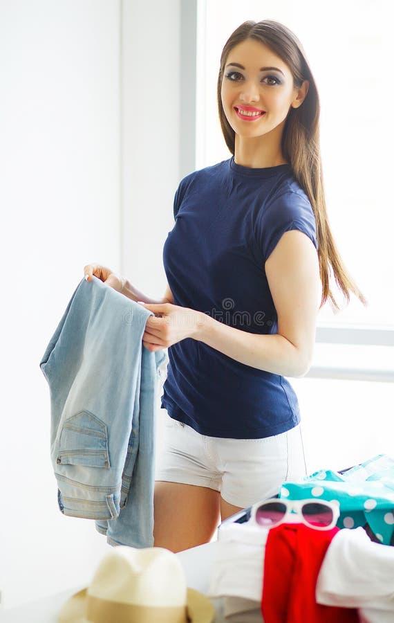 La mujer hermosa está embalando la ropa en maleta en casa fotos de archivo