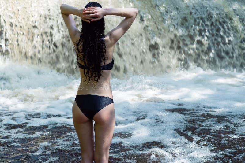 La mujer hermosa está mirando la cascada, visión trasera imagenes de archivo
