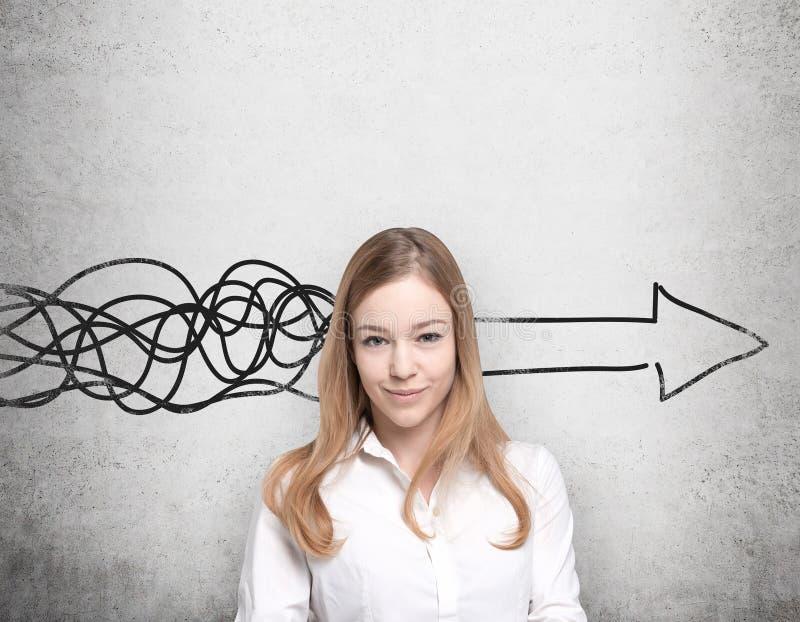 La mujer hermosa está pensando en el concepto de desarrollo de negocios Una flecha enorme se dibuja en el muro de cemento imágenes de archivo libres de regalías