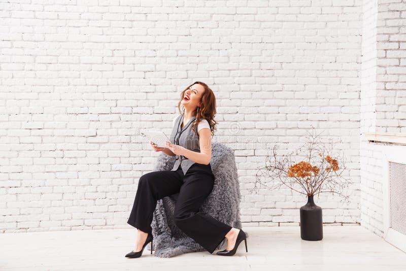 La mujer hermosa está utilizando una tableta digital y está sonriendo mientras que se sienta en la butaca en el interior moderno foto de archivo