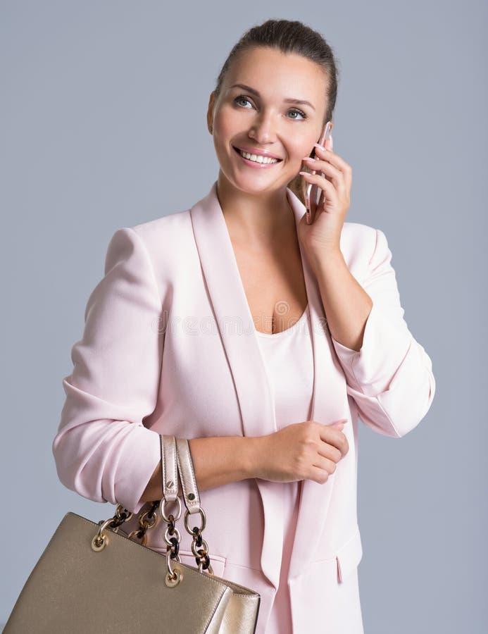 La mujer hermosa feliz sostiene el bolso y el móvil fotografía de archivo