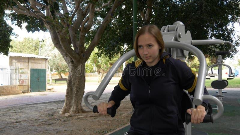 La mujer hermosa hace los excercises para las manos en el equipo de la calle foto de archivo libre de regalías