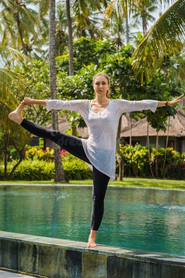 La mujer hermosa hace la práctica de la yoga, meditación, estirando la pierna en actitud permanente al borde de piscina en centro imagenes de archivo