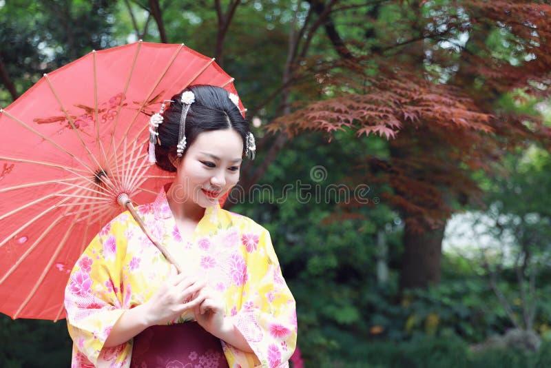 La mujer hermosa japonesa asiática tradicional del geisha lleva el control del kimono que un paraguas a mano debajo de un árbol e imagen de archivo