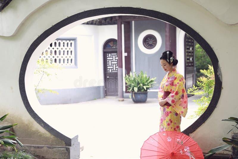 La mujer hermosa japonesa asiática tradicional del geisha lleva el control del kimono que un paraguas a mano en un verano graden imagen de archivo libre de regalías