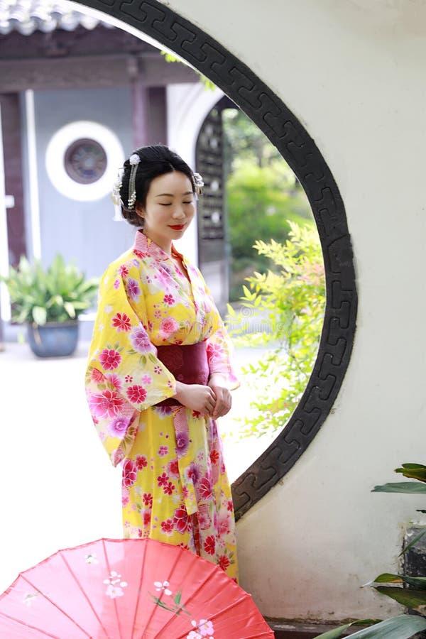 La mujer hermosa japonesa asiática tradicional del geisha lleva el control del kimono que un paraguas a mano en un verano graden imágenes de archivo libres de regalías