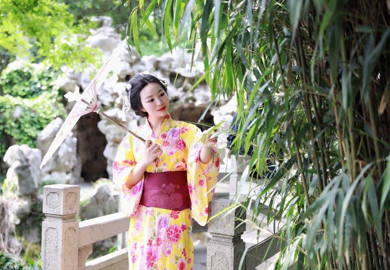La mujer hermosa japonesa asiática tradicional del geisha lleva el paraguas blanco rojo del control del kimono por el bambú en un fotografía de archivo