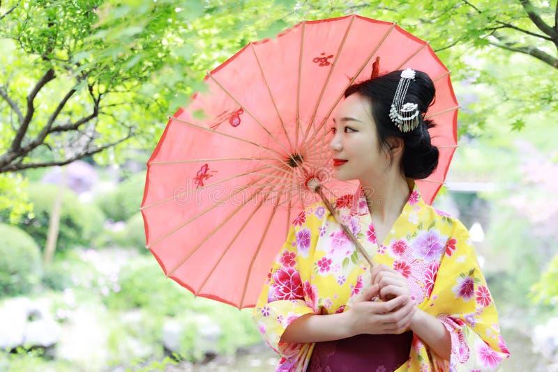 La mujer hermosa japonesa asiática tradicional del geisha lleva a la novia del kimono con un paraguas rojo en un graden foto de archivo