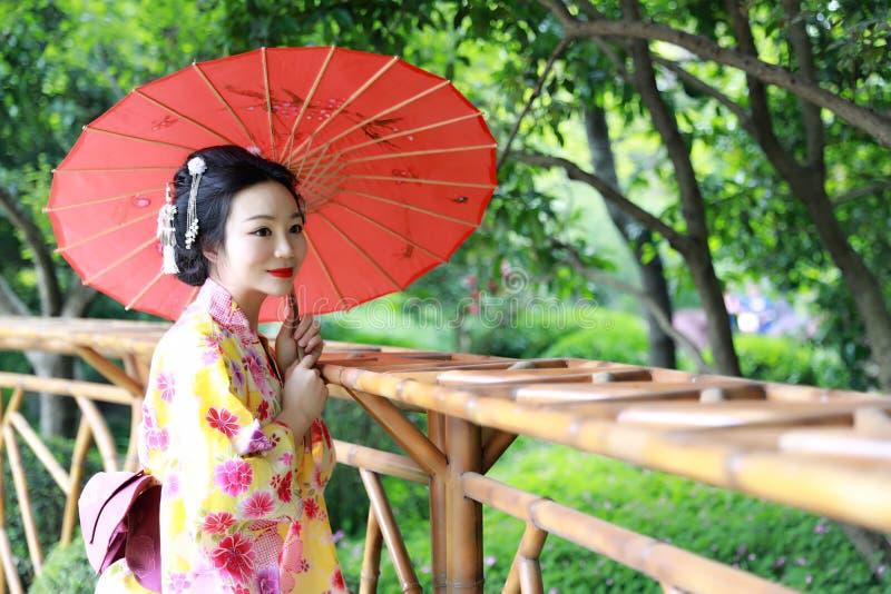 La mujer hermosa japonesa asiática tradicional del geisha lleva a la novia del kimono con un paraguas rojo en un graden fotos de archivo libres de regalías