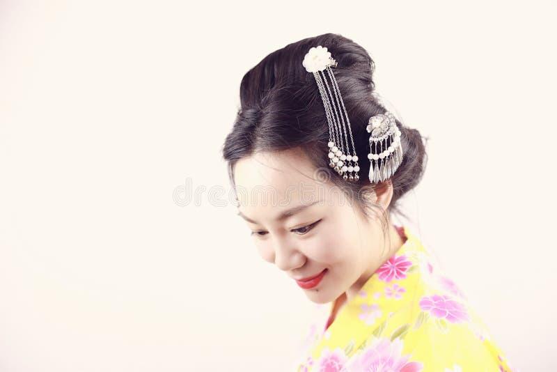 La mujer hermosa japonesa asiática tradicional del geisha lleva sonrisa del kimono en un fondo blanco aislado imagen de archivo libre de regalías