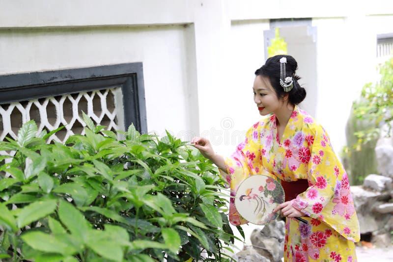 La mujer hermosa japonesa asiática tradicional lleva el kimono con jugar sonriente de la fan a mano en jardín al aire libre de la imágenes de archivo libres de regalías