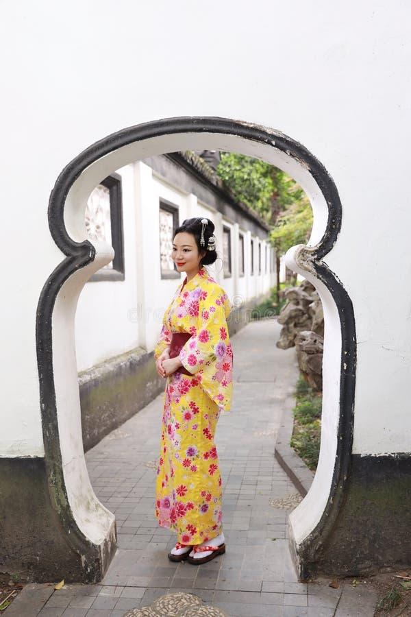 La mujer hermosa japonesa asiática tradicional lleva el kimono en un parque del jardín de la primavera hace una pausa el bambú di foto de archivo libre de regalías