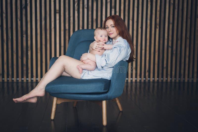 La mujer hermosa joven abraza a su bebé recién nacido imagenes de archivo