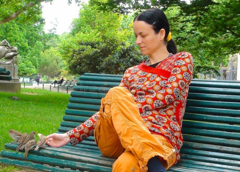 La mujer hermosa joven alimenta los gorriones en el parque Monceau, París imágenes de archivo libres de regalías