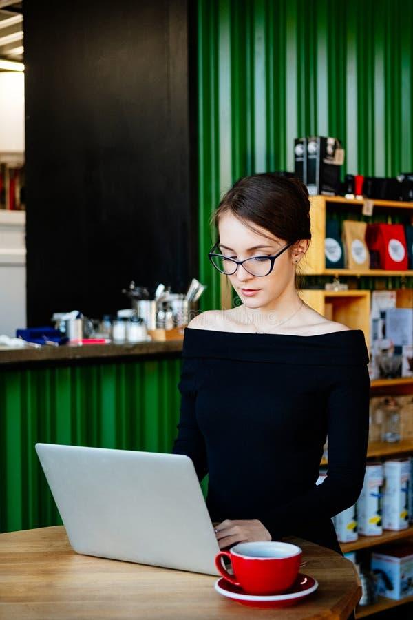 La mujer hermosa joven bonita en vidrios usando el ordenador portátil en café, se cierra encima del retrato de la mujer de negoci fotografía de archivo