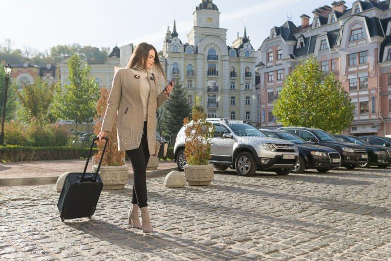 La mujer hermosa joven camina a lo largo de la calle de la ciudad con la maleta del viaje y el teléfono celular Muchacha morena d imagen de archivo libre de regalías