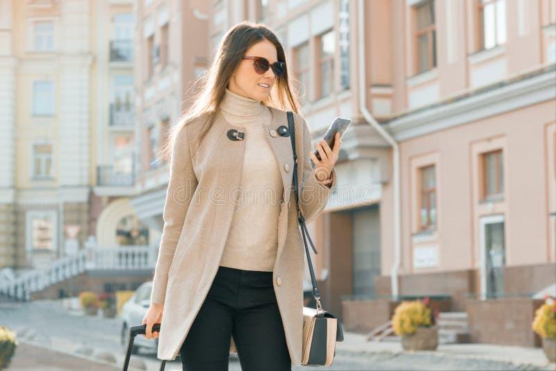 La mujer hermosa joven camina a lo largo de la calle de la ciudad con la maleta del viaje y el teléfono celular Sonrisa morena de imagen de archivo libre de regalías