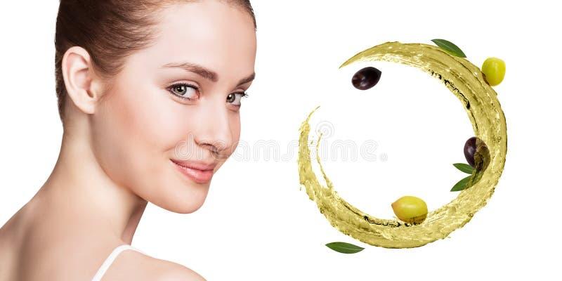 La mujer hermosa joven cerca circula el chapoteo del aceite de oliva fotos de archivo libres de regalías
