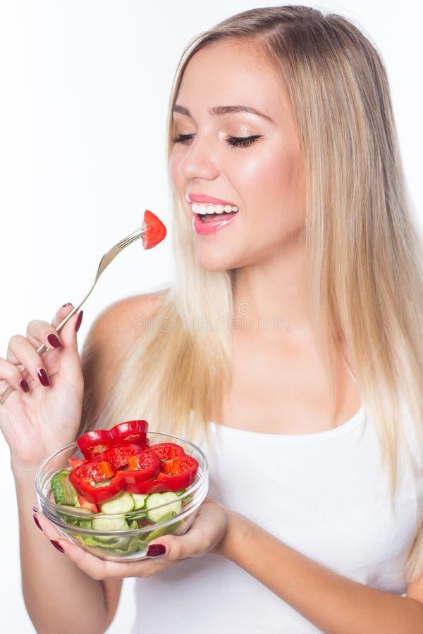 La mujer hermosa joven come la ensalada vegetal Consumición sana Para estar en forma fotografía de archivo libre de regalías