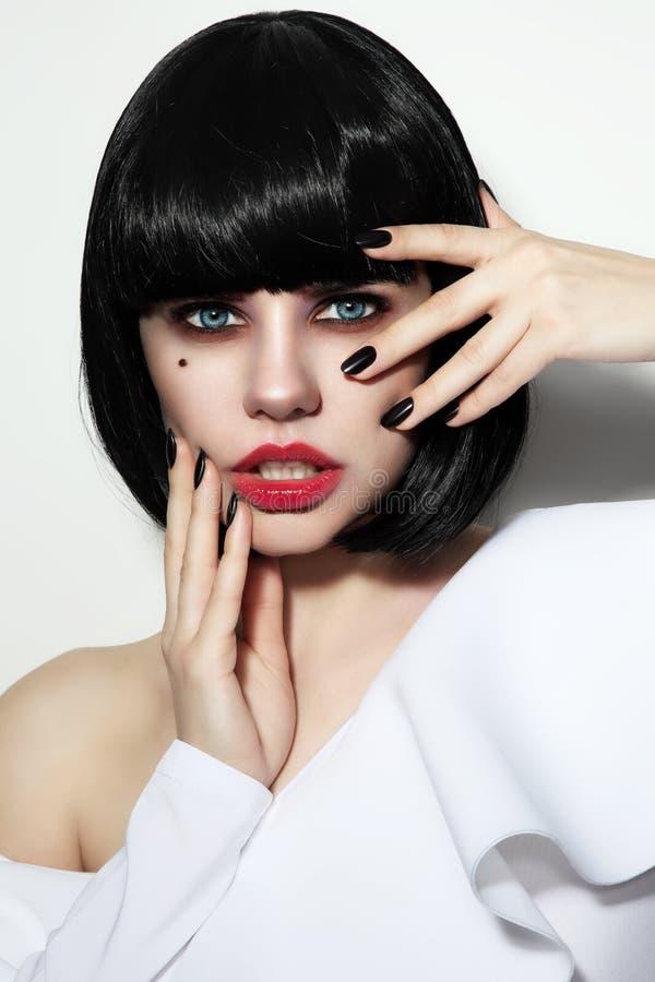 La mujer hermosa joven con corte de pelo de la sacudida, los ojos ahumados construye y s imagen de archivo