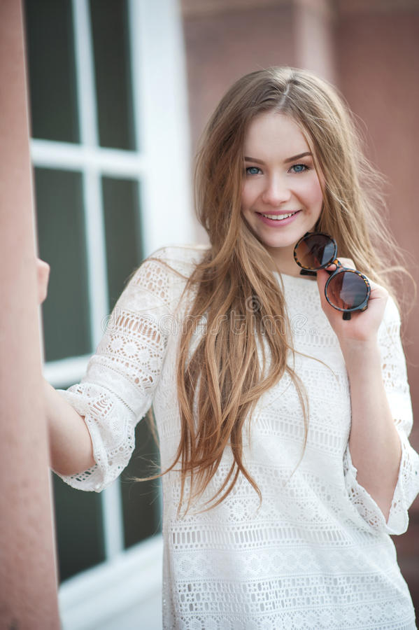 La mujer hermosa joven con el pelo largo en el vestido blanco es a sonriente foto de archivo