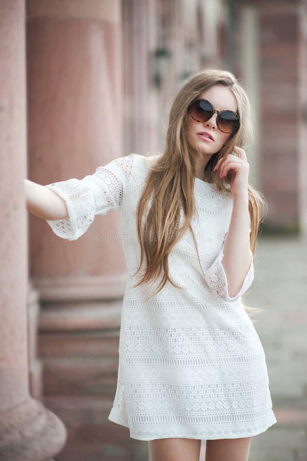 La mujer hermosa joven con el pelo largo en el vestido blanco está llevando s imágenes de archivo libres de regalías