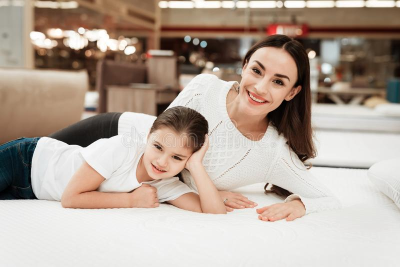La mujer hermosa joven con la niña linda miente en cama en tienda del colchón imágenes de archivo libres de regalías