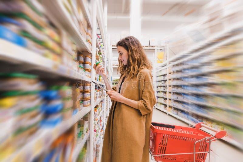 La mujer hermosa joven con una tableta escoge los alimentos para niños en un supermercado, fondo borroso imagen de archivo