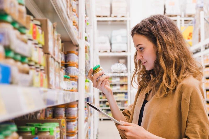 La mujer hermosa joven con una tableta escoge los alimentos para niños en un supermercado, la muchacha está estudiando la composi fotografía de archivo libre de regalías