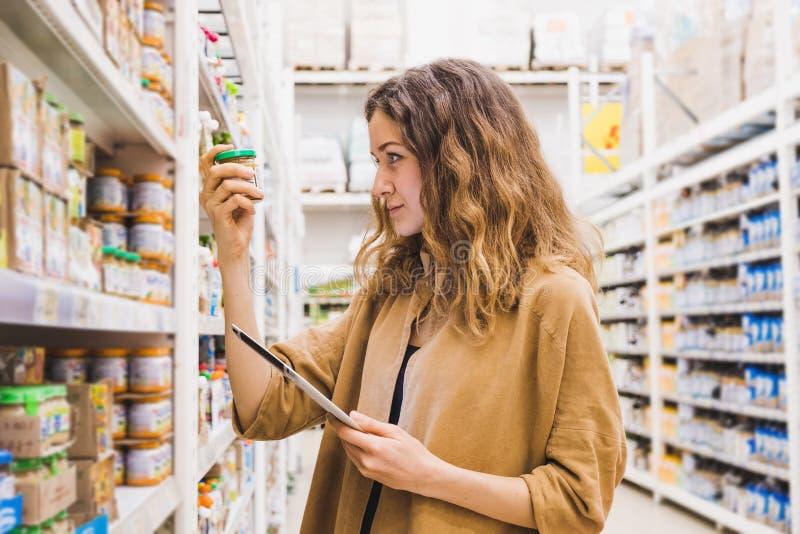 La mujer hermosa joven con una tableta selecciona los alimentos para niños en un supermercado, la muchacha lee cuidadosamente la  imágenes de archivo libres de regalías