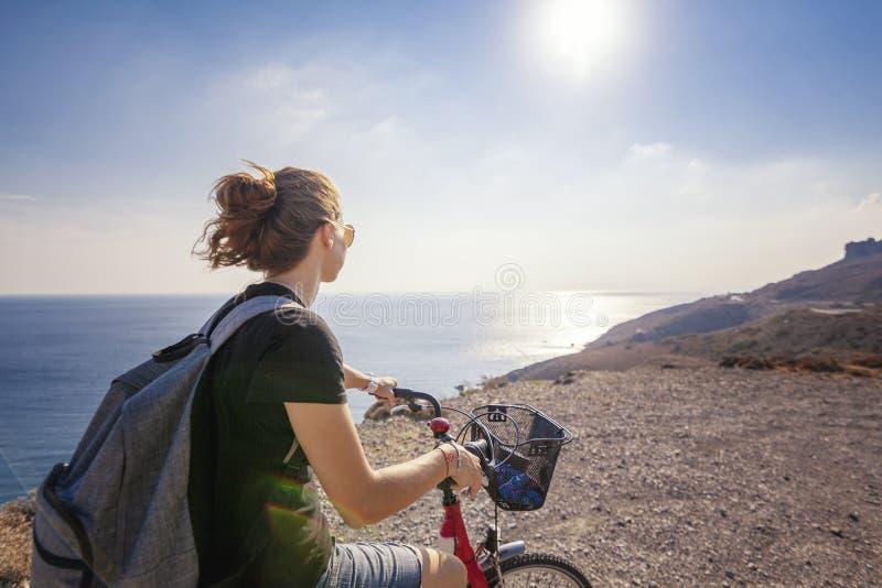 La mujer hermosa joven de la muchacha viaja en bicicleta en una tierra de la montaña imagen de archivo