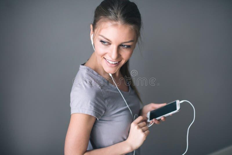 La mujer hermosa joven en auriculares con un smartphone está escuchando la música foto de archivo