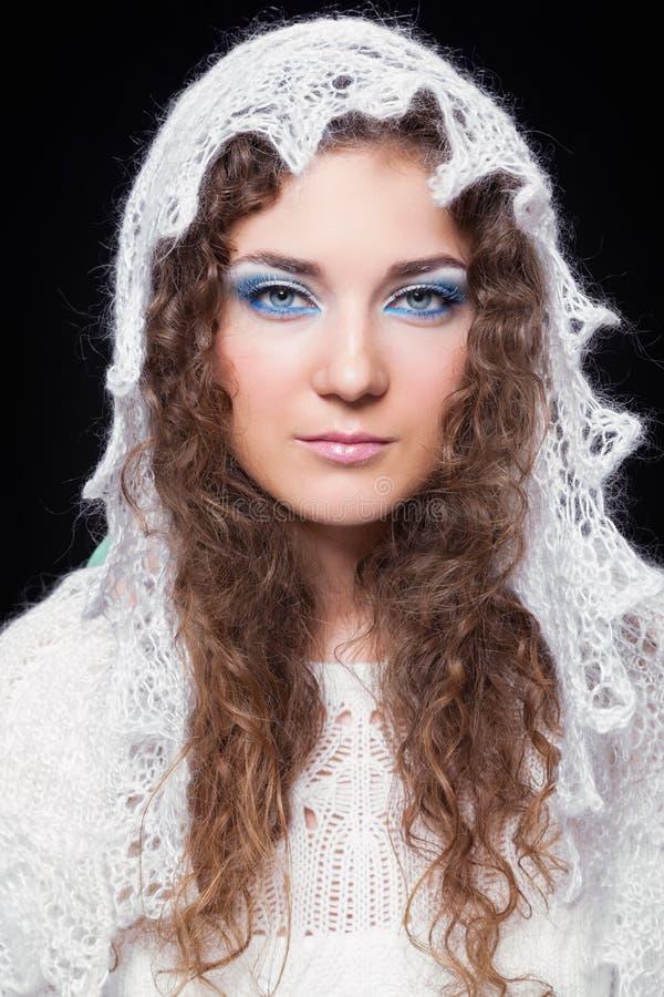 La mujer hermosa joven en blanco hizo punto la bufanda a cielo abierto imagen de archivo