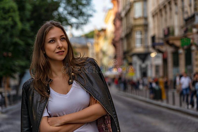 La mujer hermosa joven en la calle mira para arriba y sonríe fotos de archivo