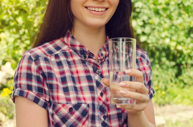 La mujer hermosa joven en camisa sport sostiene un vidrio de agua y foto de archivo libre de regalías