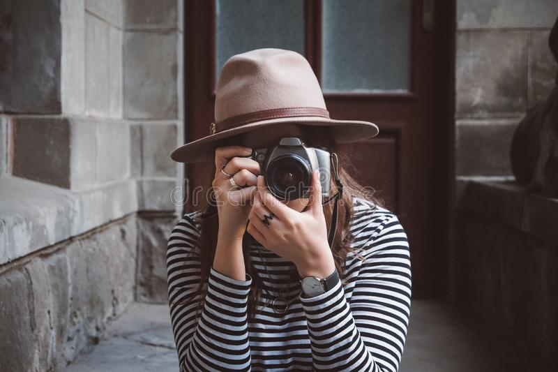 La mujer hermosa joven en sombrero está tomando la imagen con la cámara pasada de moda, al aire libre fotos de archivo