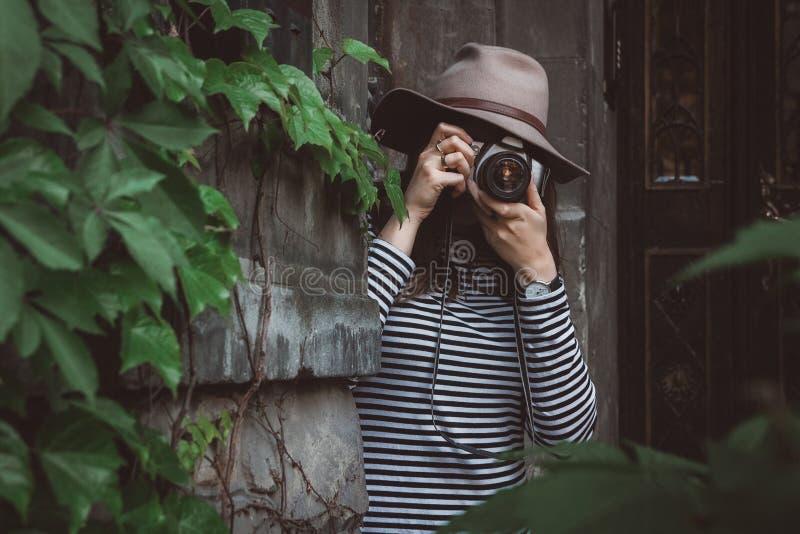 La mujer hermosa joven en sombrero está tomando la imagen con la cámara pasada de moda, al aire libre imagenes de archivo