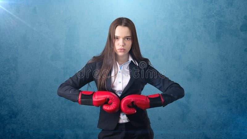 La mujer hermosa joven en traje negro y la camisa blanca que se coloca en combate presentan con los guantes de boxeo rojos Concep fotos de archivo libres de regalías